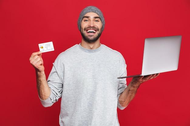 Foto de um cara feliz dos 30 anos em roupas casuais segurando um cartão de crédito e um laptop prateado isolados