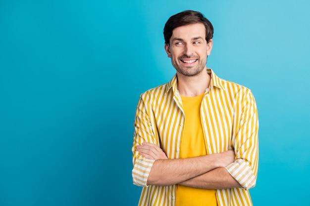 Foto de um cara inteligente feliz olhando copyspace mãos cruzadas, desfrutar de uma viagem de negócios, usar uma camisa listrada isolada sobre um fundo de cor azul