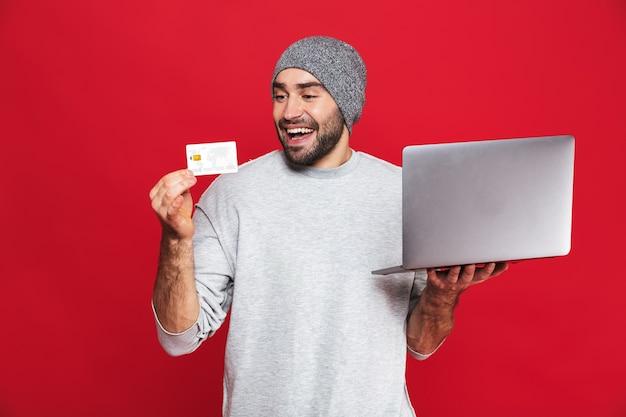 Foto de um cara positivo dos 30 anos em roupa casual segurando um cartão de crédito e um laptop prateado isolados