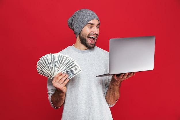 Foto de um cara rico dos anos 30 em roupa casual segurando dinheiro e um laptop prateado isolado