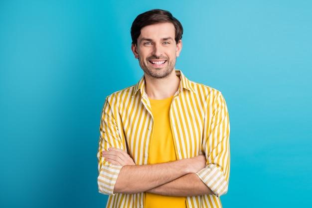 Foto de um cara satisfeito com as mãos cruzadas, pronto para uma viagem de negócios, usando uma roupa bonita isolada sobre um fundo de cor azul