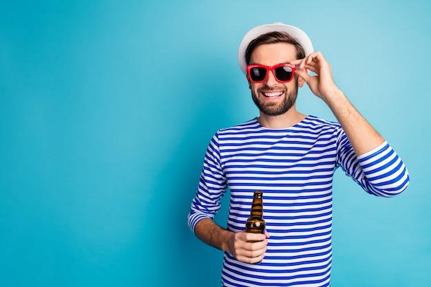 Foto de um cara simpático viajante beber cerveja garrafa tudo incluído resort exótico bom humor férias de verão usar óculos de sol listrado boné de camisa de marinheiro isolado cor azul
