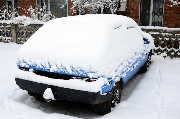 Foto de um carro coberto de uma camada grossa de neve. consequências da forte nevasca