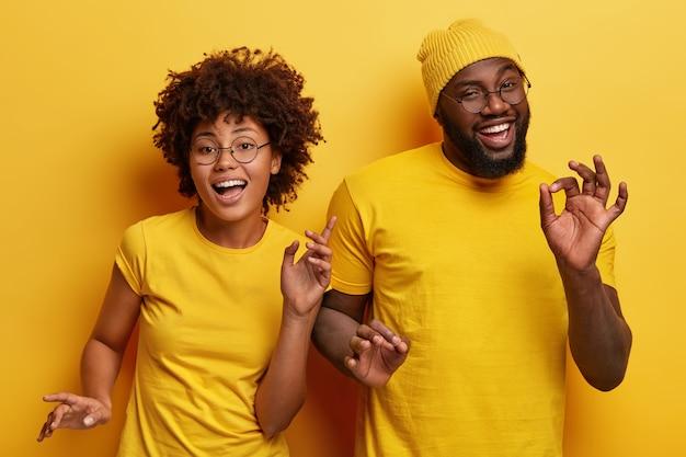 Foto de um casal africano feliz dançando juntos contra um fundo amarelo, movendo o corpo ativamente