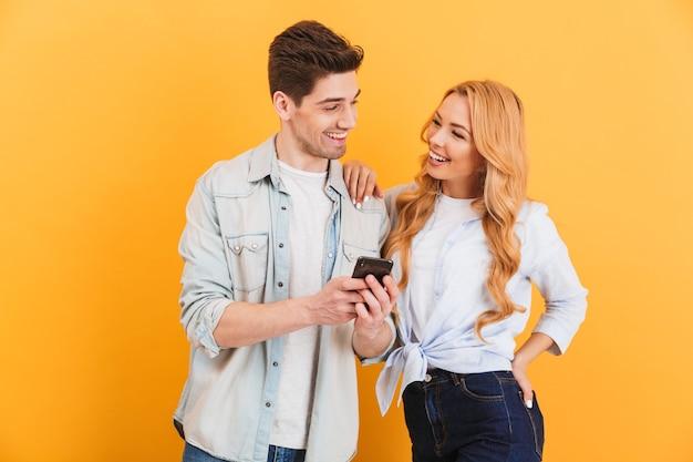 Foto de um casal alegre, homem e mulher, rindo e se olhando enquanto usam o smartphone, isolada sobre a parede amarela