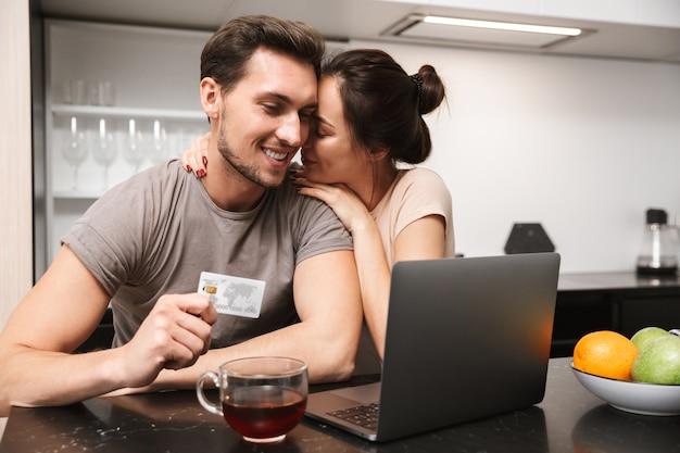 Foto de um casal atraente, homem e mulher, usando laptop com cartão de crédito, enquanto está sentado na cozinha