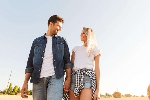 Foto de um casal caucasiano, homem e mulher, caminhando por um campo dourado com um monte de palheiros, durante um dia ensolarado