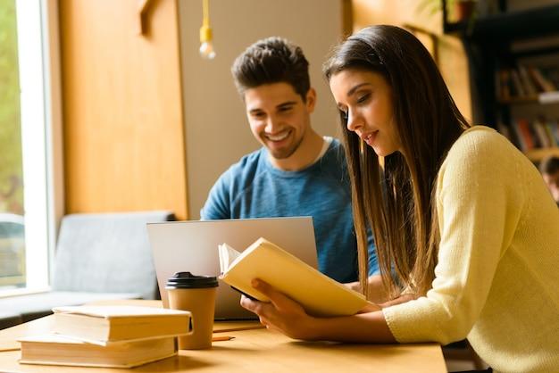 Foto de um casal de amigos de dois jovens estudantes na biblioteca, fazendo lição de casa, estudando, lendo e usando o computador portátil.
