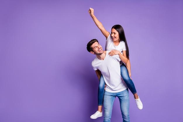 Foto de um casal de duas pessoas alegre, positivo e fofo, com o punho levantado e ele carregando-a para a frente em uma camiseta isolada com fundo de cor violeta pastel