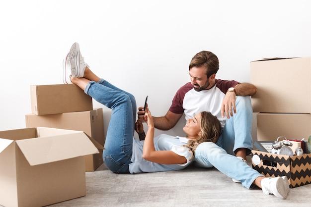 Foto de um casal engraçado com roupas casuais usando o celular, sentado perto de caixas de papelão isoladas sobre uma parede branca