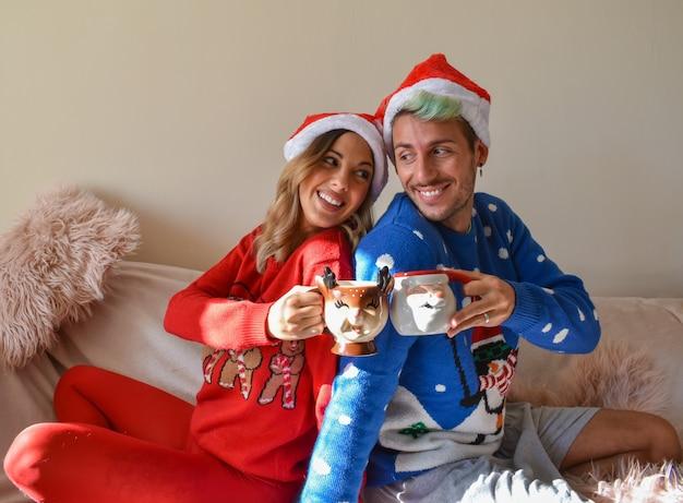Foto de um casal feliz em cabanas de natal e roupas segurando xícaras engraçadas