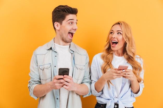 Foto de um casal feliz, homem e mulher, olhando um para o outro e segurando smartphones nas mãos