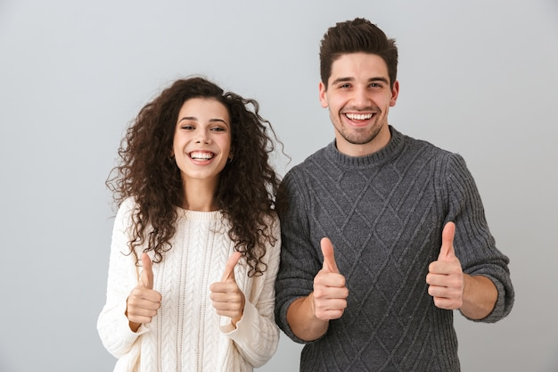 Foto de um casal feliz, homem e mulher, rindo e mostrando os polegares, isolada sobre uma parede cinza