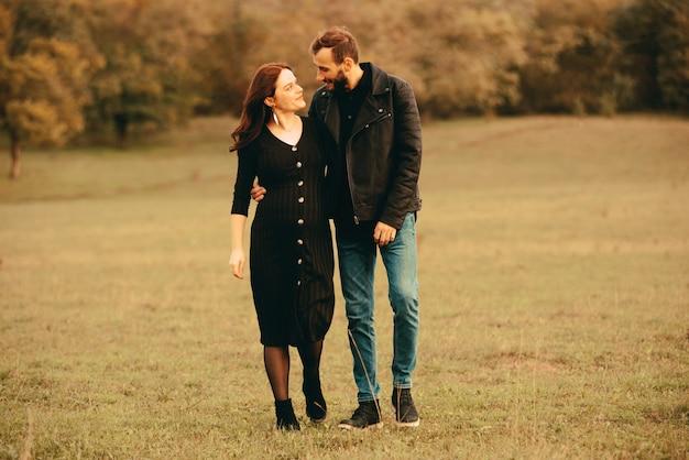 Foto de um casal grávido caminhando no parque e olhando um para o outro