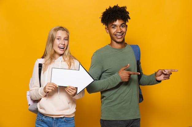 Foto de um casal multiétnico, homem e mulher de 16 a 18 anos, segurando o ponteiro de seta do copyspace, isolado sobre fundo amarelo