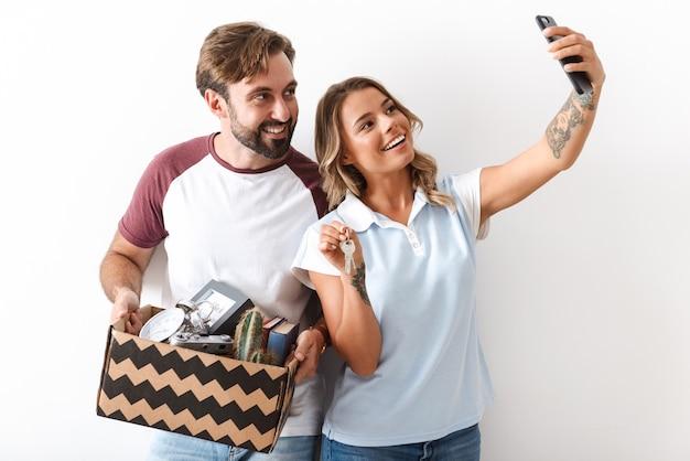 Foto de um casal sorridente em roupas casuais segurando uma caixa de papelão enquanto tira uma foto de selfie no celular isolada sobre uma parede branca