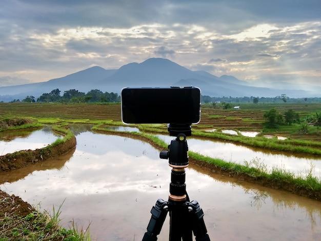 Foto de um celular com um tripé tirando fotos de vistas da montanha pela manhã