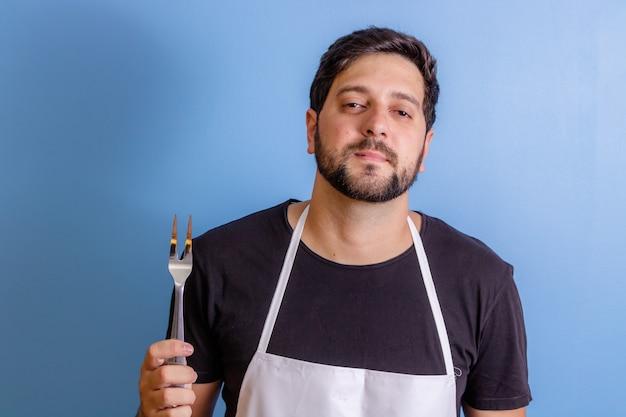 Foto de um chef feliz segurando um utensílio para cozinhar carne