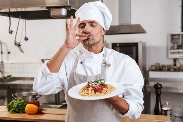 Foto de um chefe masculino bonito em uniforme branco segurando o prato com macarrão, enquanto cozinha na cozinha de um restaurante