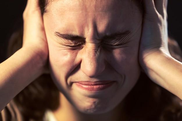 Foto de um close-up de jovem com dor de cabeça em fundo preto. conceito de doença mental.