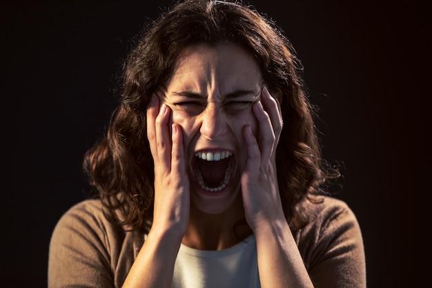Foto de um close-up de mulher jovem gritando sobre fundo preto. conceito de doença mental.