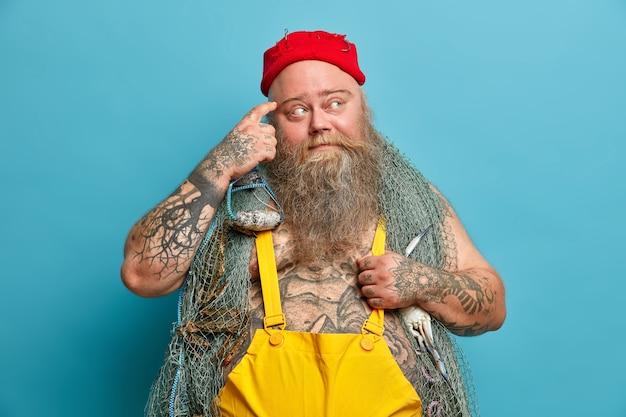 Foto de um contramestre sério esfregando a têmpora e olhando pensativamente para o lado, enquanto o corpo tatuado contempla poses