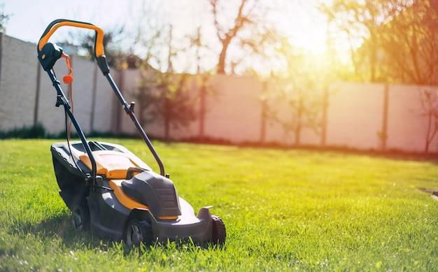 Foto de um cortador de grama elétrico moderno em pé no gramado de um quintal perto de uma casa