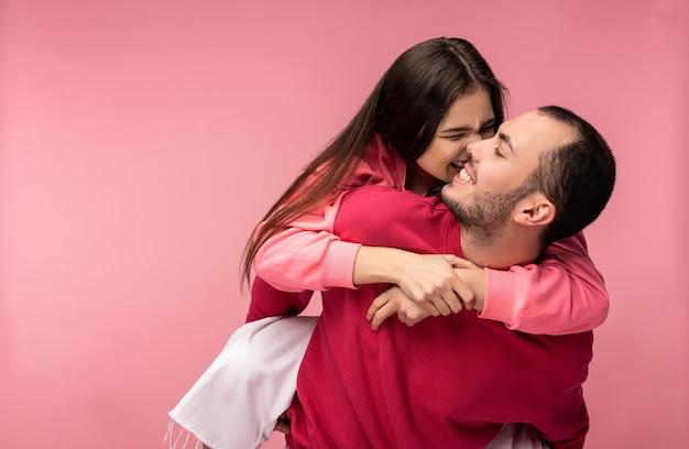 Foto de um doce casal se abraça e sorria. masculino e feminino estão apaixonados. mulher tenta morder o homem. isolado sobre o fundo rosa.