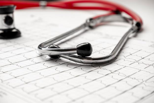 Foto de um ecg de eletrocardiograma ou impressão de ekg com estetoscópio. conceito de saúde médica. auscultação, ouvindo o pulso do coração com um estetoscópio