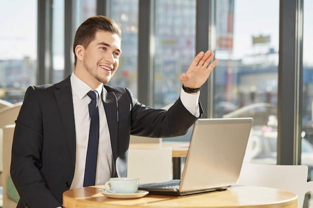 Foto de um empresário bonito alegre, trabalhando em seu laptop, chamando o garçom no café