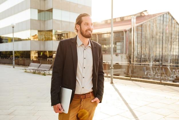Foto de um empresário com cabelo amarrado, segurando um laptop prateado e em frente a um prédio comercial em área urbana
