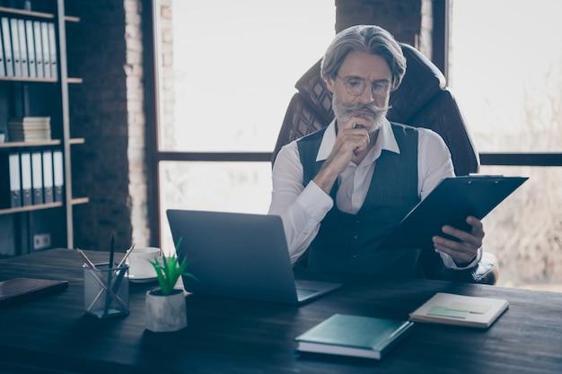 Foto de um empresário sério sentado em uma cadeira lendo uma prancheta no escritório