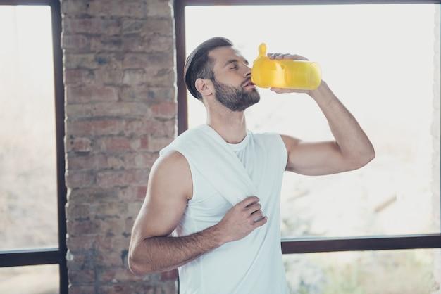 Foto de um esportista bonitão terminando o treinamento matinal bebendo água doce segurando uma toalha com os olhos fechados em roupas esportivas, janelas da casa de treino dentro