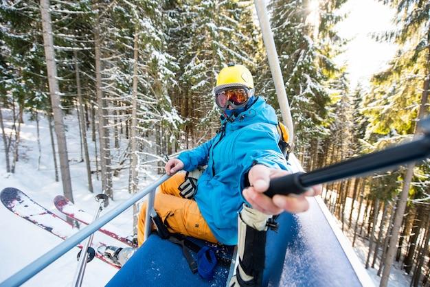 Foto de um esquiador tirando uma selfie com uma vara de selfie enquanto montava o teleférico para o topo da montanha no inverno