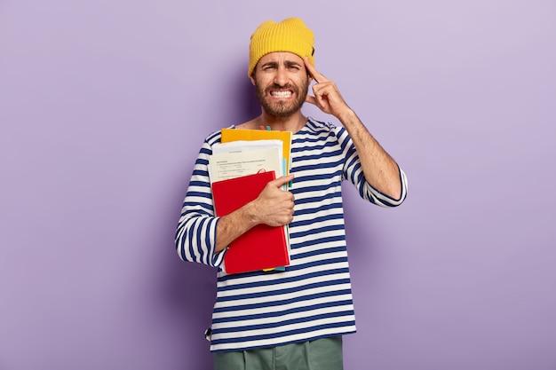 Foto de um estudante descontente trincando os dentes, sentindo dor na têmpora, segurando papéis e livros, com expressão facial perturbada, vestido com um macacão listrado casual, posa contra a parede roxa do estúdio