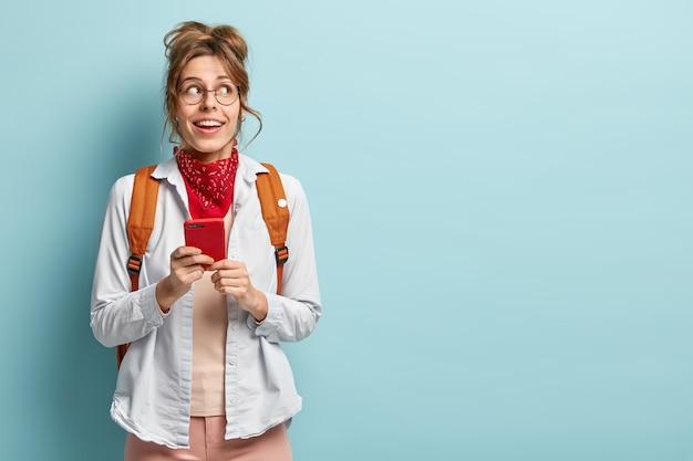 Foto de um estudante universitário alegre e pensativo segura o gadget do smartphone nas mãos, espera a conexão wi-fi, usa óculos ópticos redondos, camisa, bandana, carrega uma mochila. copie o espaço na parede azul