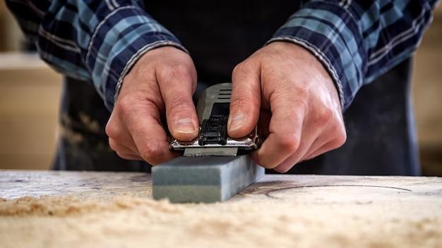 Foto de um experiente carpinteiro com roupa de trabalho, trabalhando em uma oficina de marcenaria