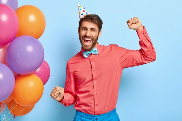Foto de um feliz aniversariante dançando na festa