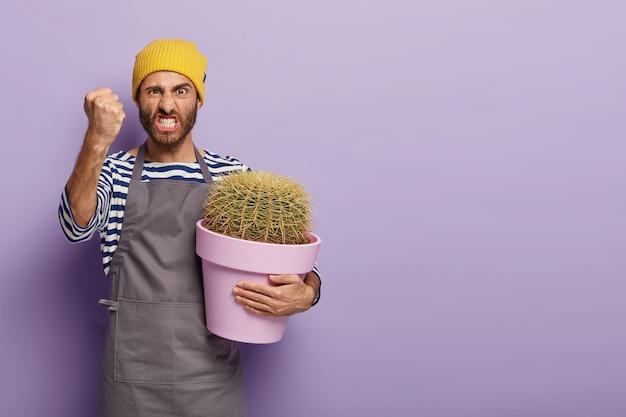 Foto de um florista europeu irritado com o punho cerrado de raiva