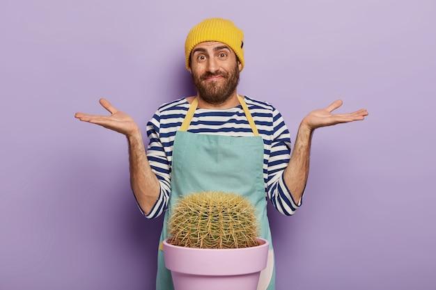 Foto de um florista masculino hesitante espalha as palmas das mãos para os lados, tem uma expressão facial desavisada, usa um uniforme especial, isolado sobre um fundo roxo. conceito de botânica