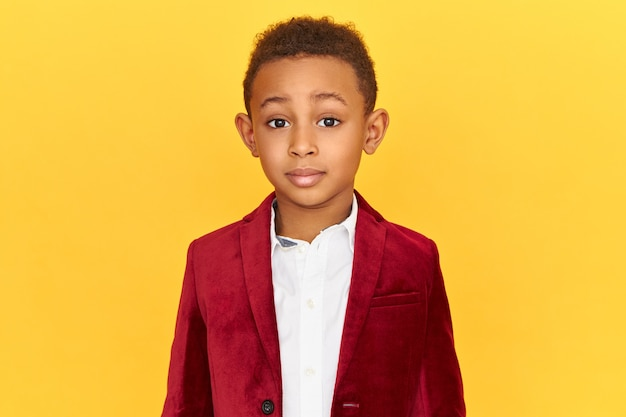 Foto de um garotinho afro-americano charmoso e fofo, vestindo roupas elegantes, posando isolado, olhando para a câmera fascinado, surpreso com os preços de venda altos
