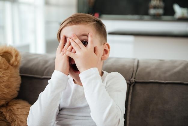 Foto de um garotinho assustado no sofá com o ursinho de pelúcia em casa assistindo tv enquanto cobre os olhos.