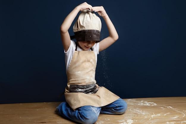 Foto de um garotinho travesso de aparência caucasiana brincando em casa, sentado no chão, usando toucas de chef, jeans e avental, despejando farinha de trigo na cabeça enquanto ajudava a mãe a fazer bolo