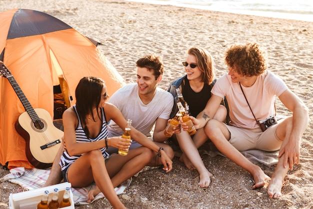 Foto de um grupo animado de amigos ao ar livre na praia, sentado enquanto bebe cerveja, conversando
