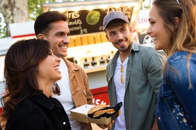 Foto de um grupo de amigos jovens atraentes conversando enquanto visitava o mercado de comer na rua.