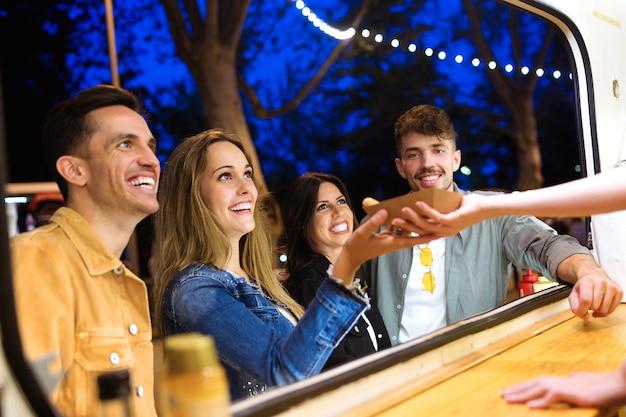 Foto de um grupo de jovens amigos atraentes, escolhendo e comprando diferentes tipos de fast food em comer mercado na rua.