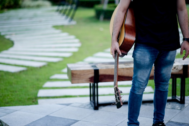 Foto de um guitarrista, um jovem tocando violão enquanto está sentado em um jardim natural