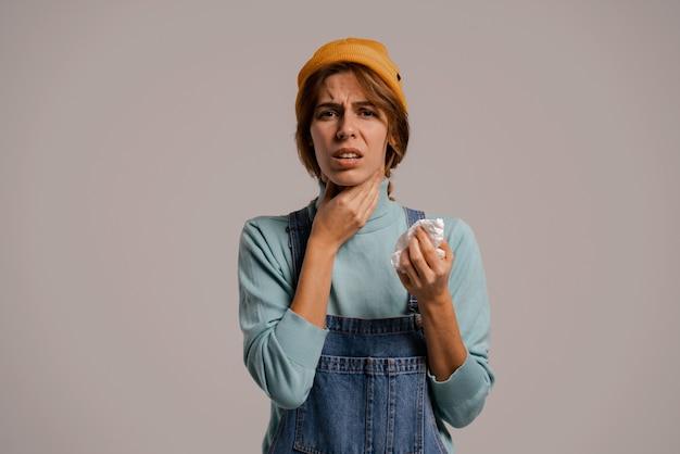 Foto de um hipster feminino bonito tem dor de garganta e parece que ficou doente. mulher branca usa macacão jeans e fundo de cor cinza com chapéu isolado.