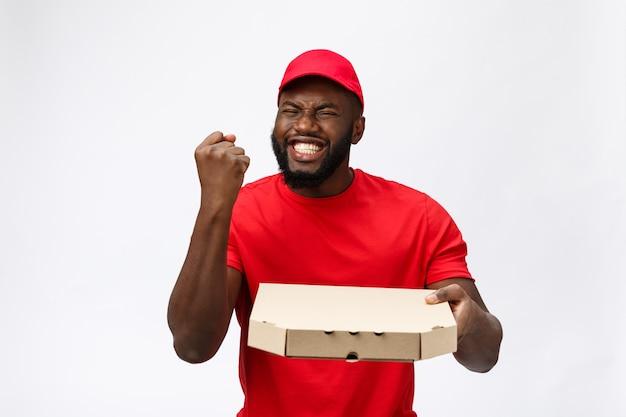 Foto de um homem afro-americano feliz do serviço de entrega em camiseta vermelha e boné dando pedido de comida e segurando uma caixa de pizza