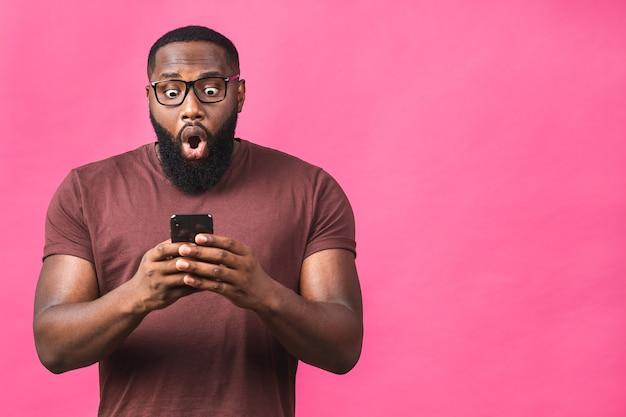 Foto de um homem afro-americano muito feliz, sabendo que ele se tornou o vencedor de algo tão regozijante, apreciando informações de notícias enquanto isolado sobre o fundo rosa.